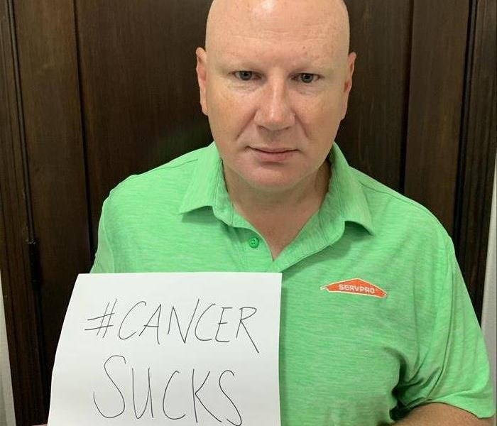 "A man wearing a green shirt holding a sign that says ""Cancer Sucks"""