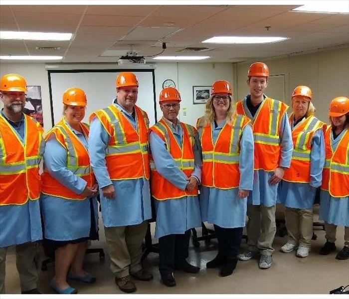 4 women and 4 men wearing neon orange safety vests posing for a group photo after the tour