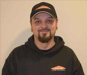 A man wearing a black SERVPRO hat and hoodie.