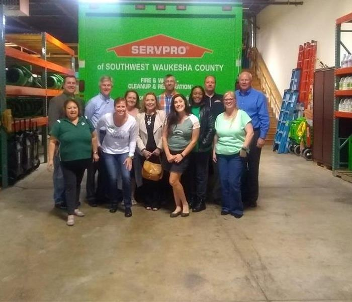 A group of people standing in front of a green SERVPRO box truck