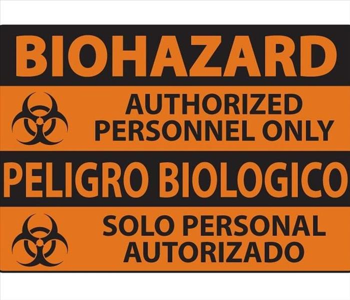 Biohazard authorized personnel only sign written in English and Spanish