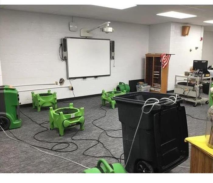SERVPRO equipment is sitting in a school classroom after a water loss, there is a lot of equipment