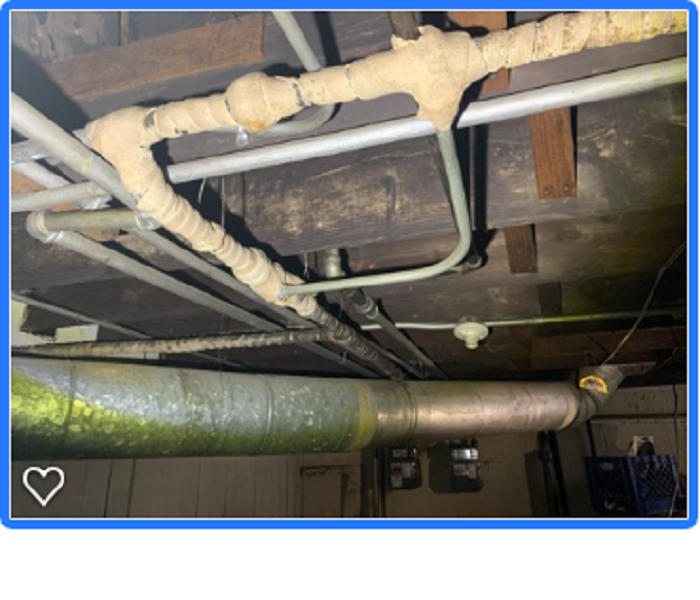 Pipes hanging from ceiling wrapped with insulation