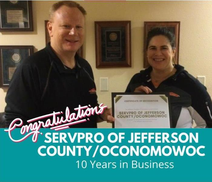 Both owners of SERVPRO holding a 10 year business anniversary certificate